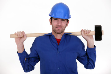 craftsman in blue overalls holding huge hammer