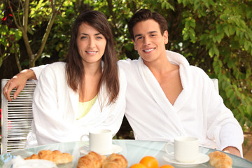 Young couple having breakfast outside