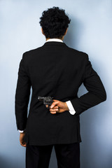 Businessman hiding gun behind his back