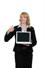 Businesswoman holding a laptop and giving the thumb's up