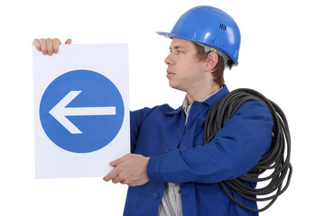 Electrician with a road sign