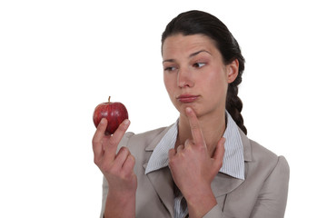 woman holding an apple and thinking