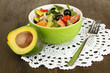 Tasty avocado salad in bowl  on wooden table close-up