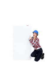 Construction worker pointing at poster.
