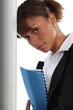 A cute black businesswoman holding a file.
