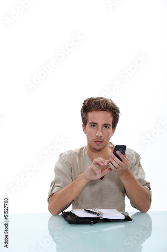 Man sitting a desk with a cellphone and personal organizer