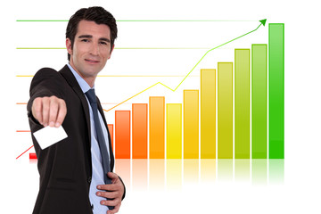 Businessman with calling card standing by bar chart