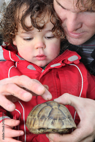 Father and son with a tortoise