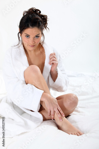 Woman wearing bathing-gown sat on bed