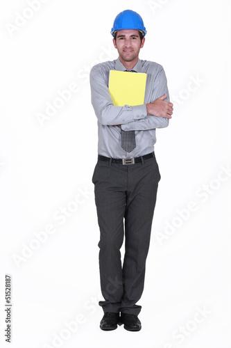 Man with helmet holding report