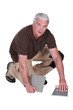 Man cementing tile to floor