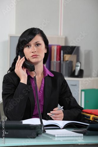 Receptionist writing note for boss