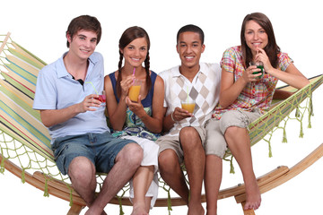 Friends drinking cocktails on a hammock