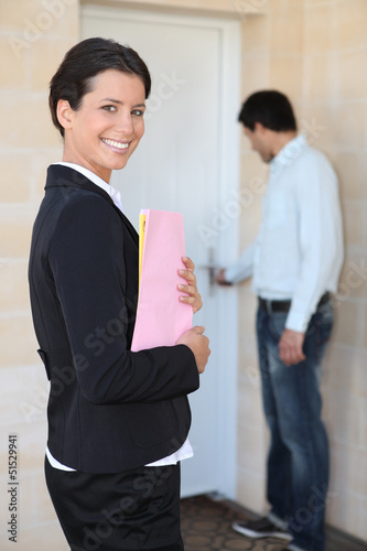 female realtor all smiles on doorstep with young client