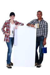 two painters holding a white ad board
