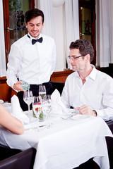 Kellner schenkt Wasser ein Dinner Restaurant