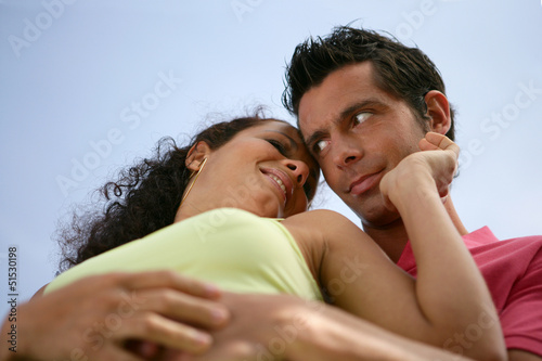 Low-angle view of couple stood hugging outdoors