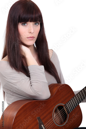 Gorgeous woman holding guitar