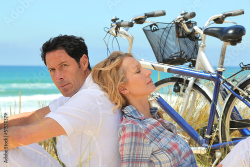 couple with bikes on the beach