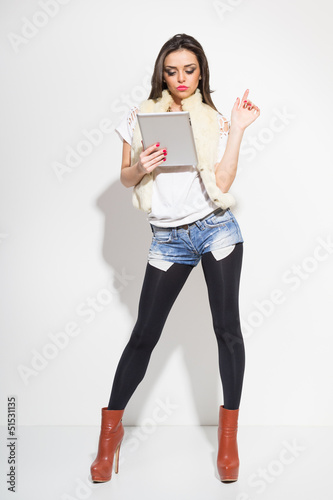 Sexy fashionable young woman using digital tablet