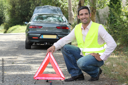 Man putting out a hazard triangle