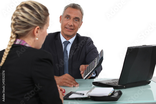 smiling mature businessman and young blonde assistant