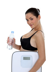 Brunette holding bottle of water and scales