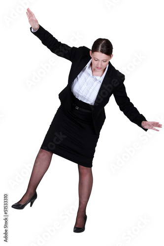 female businesswoman miming tightrope walker