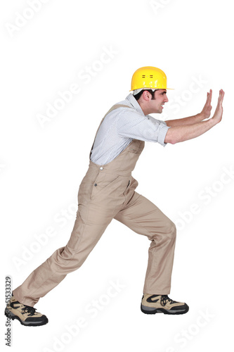 Foreman pushing hard against a wall