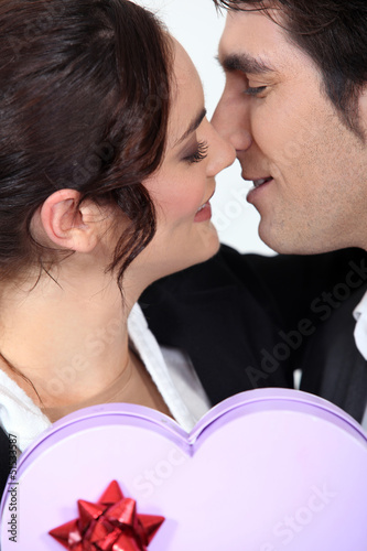 Man offering girlfriend heart-shaped box of chocolates