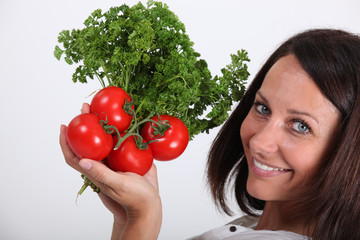 Woman holding bunch of tomatoes