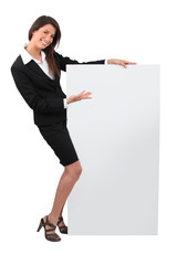 Portrait of woman in skirt suit with blank board