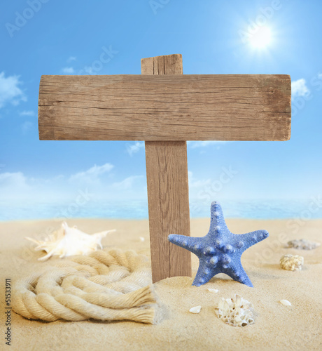 Signboard on the beach with sun and sky near sea