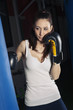 Punching boxing woman portrait in the gym.