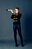 Beautiful girl in the old-fashioned uniform  holds a spyglass.
