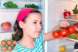 Mädchen mit Tomaten vor einem offenen Kühlschrank