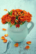 Bouquet of orange roses in a blue vase