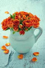 Bouquet of orange roses in a blue vase