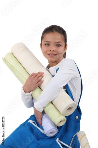 Little girl holding wallpaper rolls