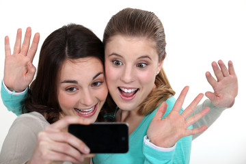 Two girls posing with camera phone