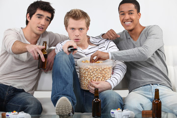 Three male friends watching television together