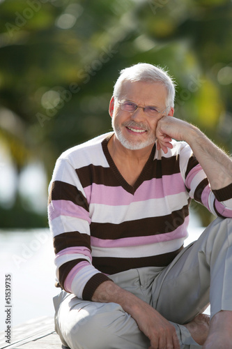 Elderly man sat in garden