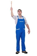 Man with paint brush raising arm