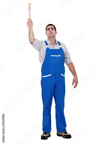 Man with paint brush raising arm