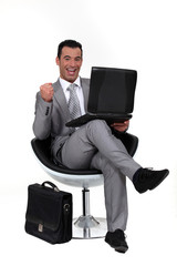 Successful man sat in chair with laptop