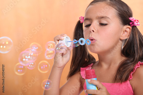 Girl blowing bubbles of soap