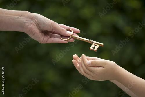 Leinwanddruck Bild adult hands key to child