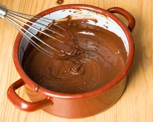 Topf mit Schneebesen und geschmolzener Schokolade auf Holz