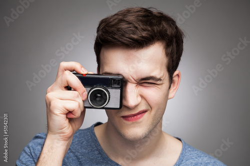 Young man with vintage camera