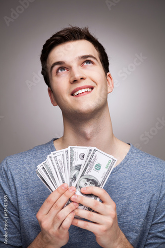 Man with money looking up